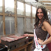 National Cherry Queen and NMC alumna Meg Howard tries her hand at flipping some buffalo burgers.