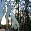 The Spirit Form sculpture stands still as sunlight pours over the Beckett building